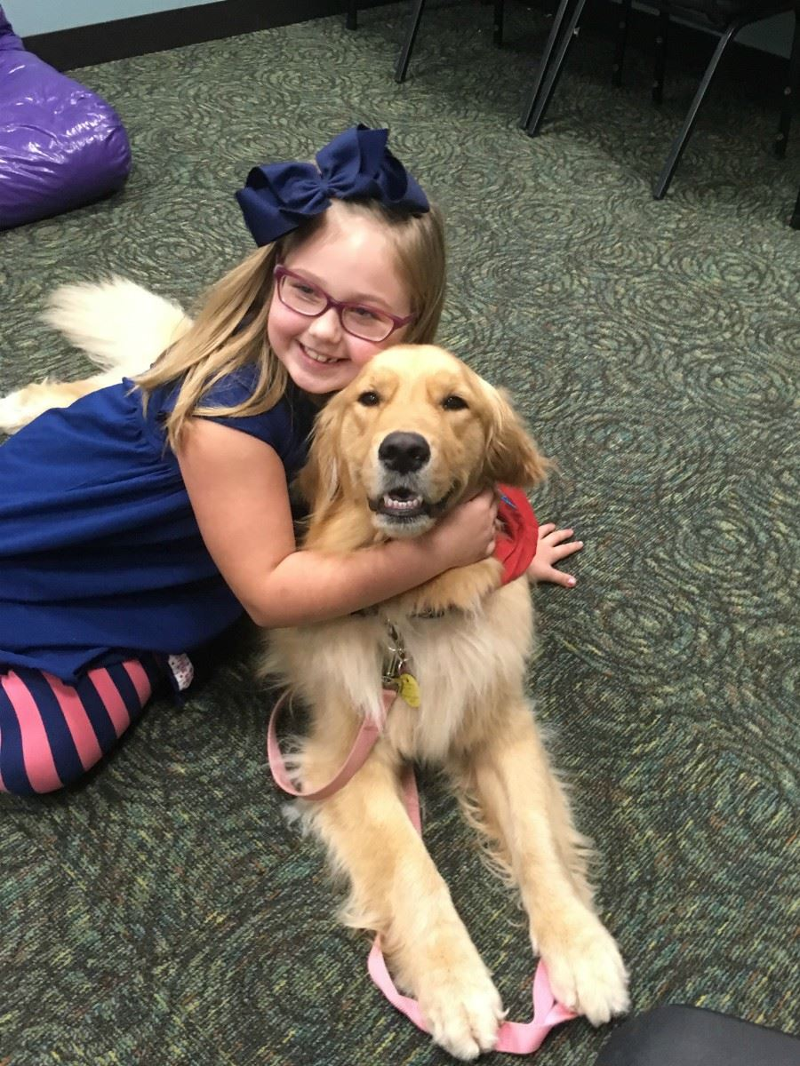 Tail Waggin Tutor being hugged by young girl